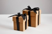 cardboard gift boxes with black ribbons isolated on grey, black Friday concept