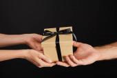 oříznutý pohled na muže a ženu držící kartónovou dárkovou krabici se stuhou izolovanou na černé, černý páteční koncept