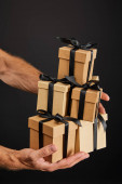 cropped view of man holding cardboard gift boxes with ribbons isolated on black, black Friday concept