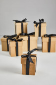 selective focus of cardboard gift box with black ribbon isolated on grey, black Friday concept