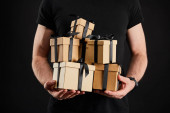 partial view of man holding cardboard gift boxes with ribbons isolated on black, black Friday concept