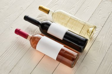 Bottles with red, white and rose wine on white wooden surface stock vector
