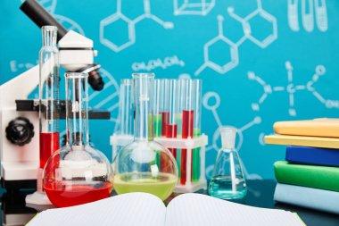 mikroskop, cam test tüpleri ve fotokopi defterinin yanında renkli sıvıyla mataralar ve moleküler yapısı olan mavi arkaplan üzerine kitaplar.