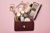 top view barna táska közelében dekoratív kozmetikumok és óra elszigetelt rózsaszín