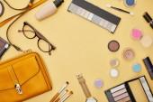 vrchní pohled na tašku v blízkosti dekorativní kosmetiky a skla izolované na žluté