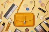 top view of bag near decorative cosmetics and necklace isolated on yellow