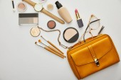 top view of yellow bag near decorative cosmetics isolated on grey