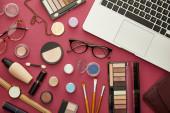 top view laptop közelében dekoratív kozmetikumok és szemüveg a bíbor