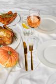 ganzer Kürbis, gegrillte Hähnchen und gebackene Karotten in der Nähe von Gläsern mit Rosenwein und Zitronenwasser auf weißer Tischdecke