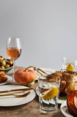 Fotografie whole pumpkin near grilled turkey, and glasses with rose wine isolated on grey