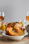 Fotografie selective focus of sliced baked pumpkin near grilled turkey and glasses with rose wine isolated on grey