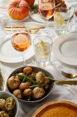 festive dinner with baked seasonal vegetables near glasses with rose wine and lemon water served on white tablecloth