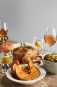 Fotografie sliced baked pumpkin near grilled turkey and glasses with rose wine on stone table isolated on grey