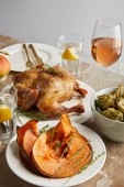 Fotografie grilled whole turkey near baked sliced pumpkin and bowl with physalis near glasses with rose wine and lemon water isolated on grey