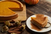 Photo delicious pumpkin pie with cinnamon powder near physalis and cinnamon sticks on dark wooden surface