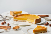 white plates with tasty pumpkin pie near cutlery and spices isolated on grey