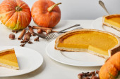 Photo white plates with tasty pumpkin pie near whole pumpkins, cutlery and spices isolated on grey