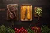Blick von oben auf Fleisch, Mais, Chilischoten, Kirschtomaten, grüne Erbsen, Grün, Rosenkohl auf Schneidebrett