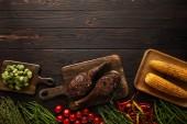 vrchní pohled na maso, kukuřici, chilli papričky, cherry rajčata, hrách, zeleň, bruselské výhonky na řezné desce