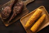 vrchní pohled na chutné maso a kukuřici na řezacích prknech