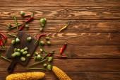 vrchní pohled na kukuřici, chilli papričky, hrách zelený, bruselské výhonky na řezací desce