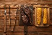 Ansicht von Fleisch, Mais auf Schneidebrettern und Grillgeräten