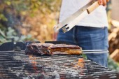 cropped view of man with tweezers grilling meat on barbecue grid