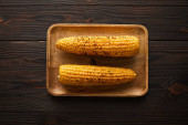 vrchní pohled na chutnou a organickou kukuřici na dřevěné desce