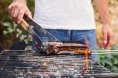 ořezaný pohled na muže s pinzetou grilující maso na grilu