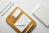 pohled shora na obálku, vizitku a pero na dřevěné desce, notebook, tužky