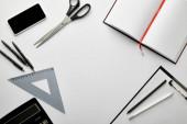 horní pohled na schránku, notebook, pera, tužky, nůžky, trojúhelník pravítko, kalkulačka, smartphone