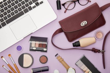 Top view of bag and decorative cosmetics near laptop isolated on violet stock vector