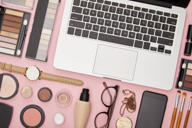 Top view of laptop near decorative cosmetics and glasses isolated on pink stock vector