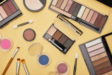 Top view of set with brown eye shadow near cosmetic brushes isolated on yellow stock vector