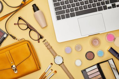Top view of laptop near glasses and decorative cosmetics isolated on yellow stock vector