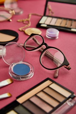 Selective focus of glasses near decorative cosmetics on crimson stock vector