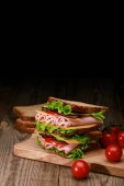 fresh sandwich with lettuce, ham, cheese, bacon and tomato on wooden cutting board with cherry tomatoes isolated on black