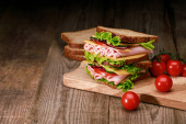 fresh sandwich with lettuce, ham, cheese, bacon and tomato on wooden cutting board with cherry tomato