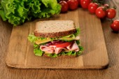 selective focus of fresh sandwich on wooden cutting board near lettuce and cherry tomatoes