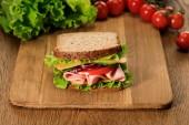 szelektív összpontosítás friss szendvics fa vágódeszka közelében saláta és cseresznye paradicsom