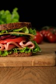 close up view of fresh sandwich with lettuce, ham, cheese, bacon and tomato on wooden cutting board isolated on black