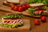 selective focus of fresh sandwich with lettuce, ham, cheese, bacon and tomato on wooden cutting board