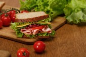 selective focus of sandwich on wooden cutting board near fresh cherry tomatoes and lettuce