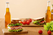 selective focus of fresh sandwich with lettuce, ham, cheese, bacon and tomato near bottles of beer at wooden table isolated on beige