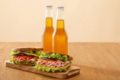 fresh sandwiches with lettuce, ham, cheese, bacon and tomato near bottles of beer at wooden table isolated on beige