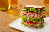 selective focus of fresh sandwich with lettuce, ham, cheese, bacon and tomato near bottles of beer at wooden table