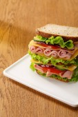 fresh sandwich with lettuce, ham, cheese, bacon and tomato at wooden table