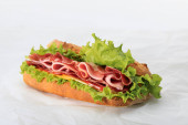 fresh sandwich with lettuce, ham, cheese, bacon and tomato on textured white background