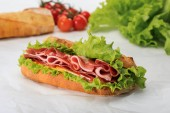 selective focus of fresh sandwich with lettuce, ham, cheese, bacon and tomato on textured white background