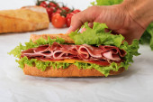 cropped view of man holding fresh sandwich with lettuce, ham, cheese, bacon and tomato on textured white background
